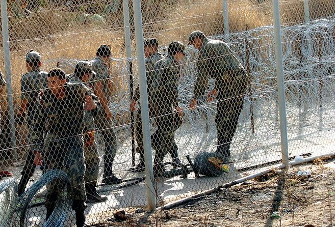 Militares participan en la instalación de la concertina en la valla...