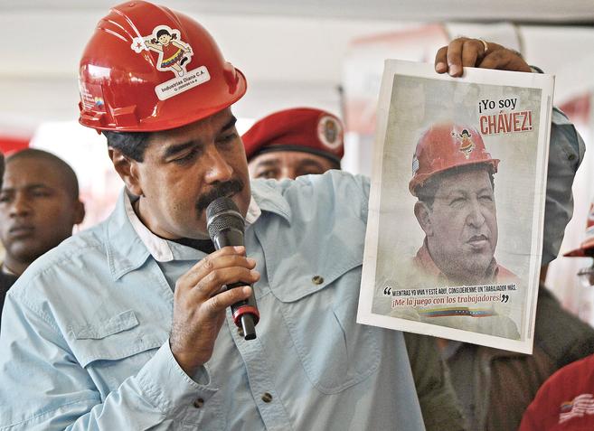 Nicolás Maduro muestra un retrato de Chávez en Caracas durante un...
