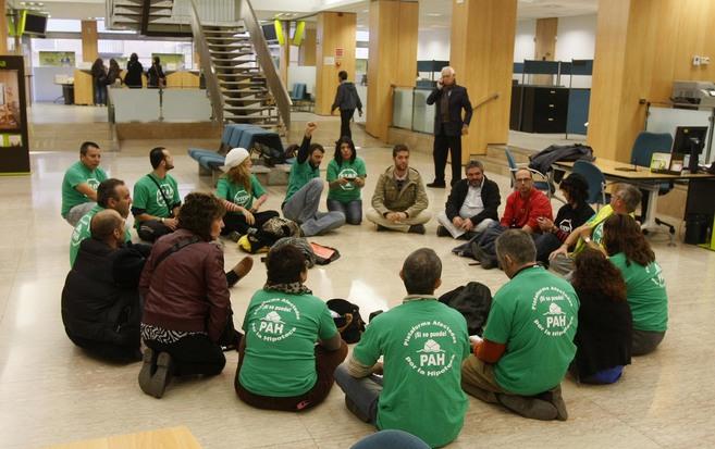 Los ocho afectados junto a activistas de la PAH en la sucursal de...