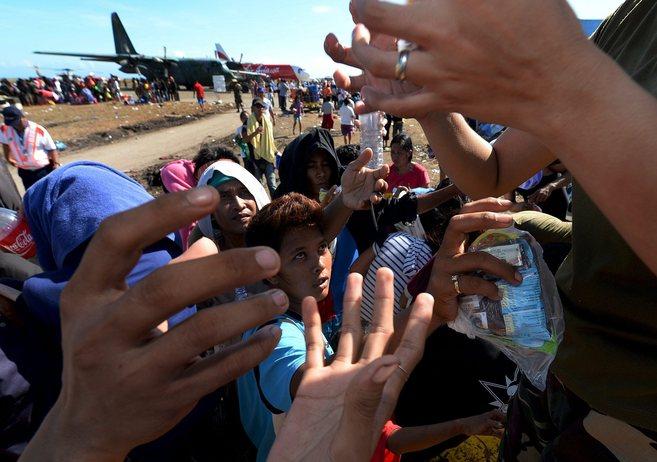 Supervivientes del tifón intentan conseguir ayuda.