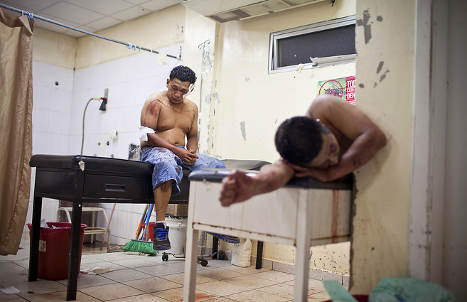 Dos hombres heridos esperan a ser atendidos en el hospital Mario...