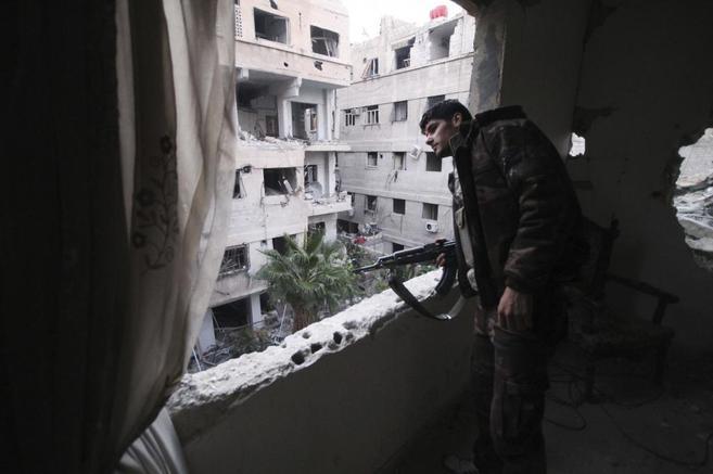 Un miembro del Ejército Libre de Siria defiende un edificio en...