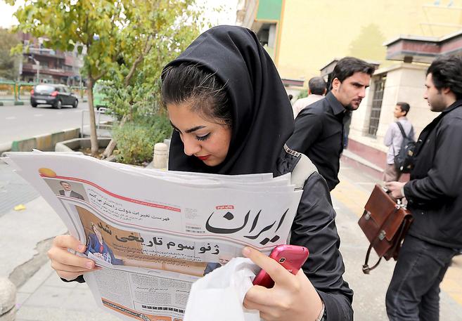Una joven iraní lee la información publicada en un diario sobre el...