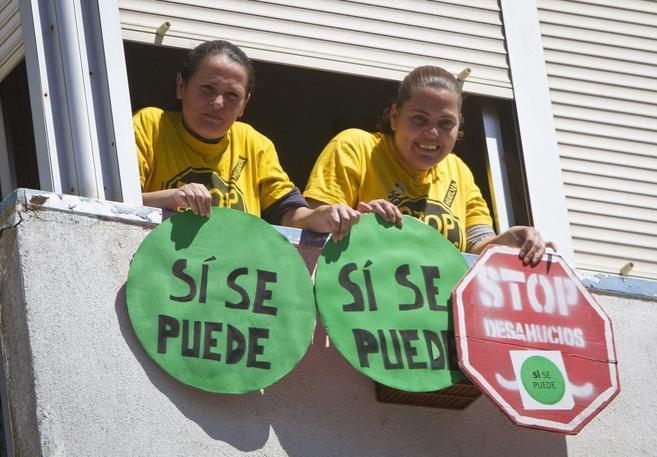 Dos mujeres muestran carteles en contra de los desahucios desde una...