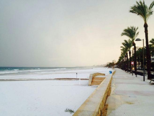 La playa de El Campello, cubierta por un manto blanco de granizo, a...