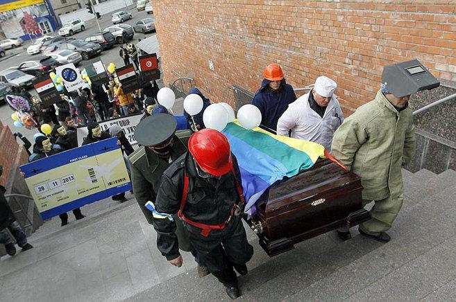 Un grupo de manifestantes transporta un féretro como símbolo de la...