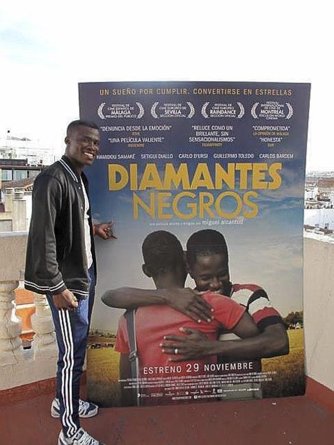 Alassane Diakité posa delante del cartel de la película.