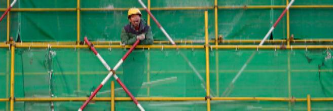 Un trabajador chino, en un andamio de un edificio en construcción de...