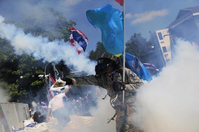 Un manifestante antigubernamental arroja gas lacrimógeno a la...