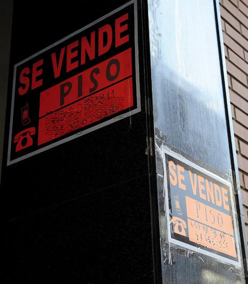 Varios carteles de se vende en la entrada a un edificio.