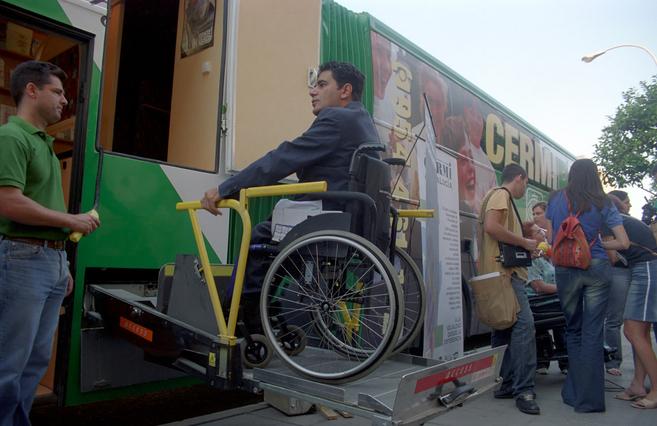 Una persona con discapacidad sube la rampa de un autobús.