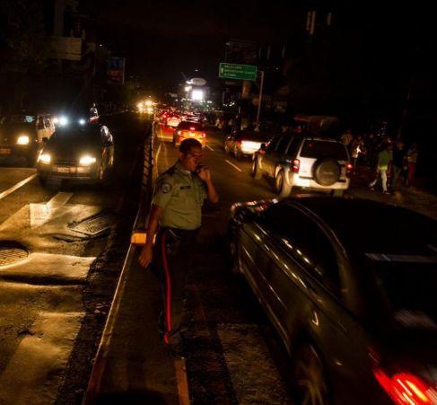 Un agente intenta poner orden en una calle sin luz en Caracas.