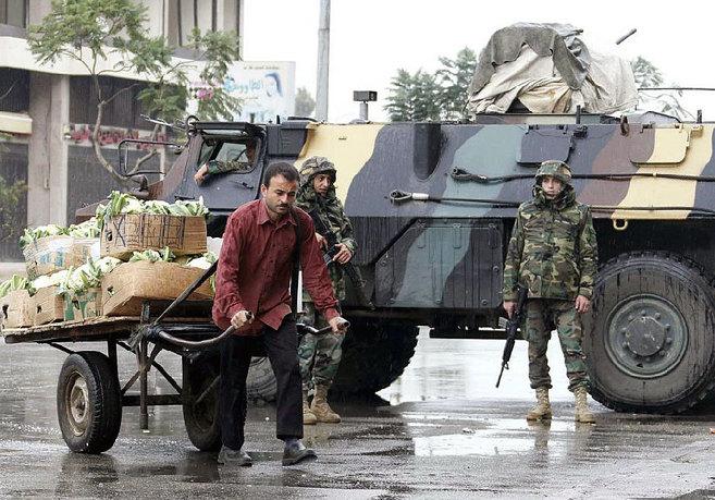 Un repartidor de verduras camina por Trípoli bajo la atenta mirada...
