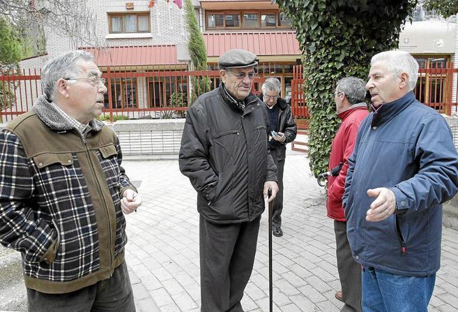 Un grupo de pensionistas conversa a las puertas de un centro para la...