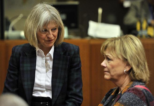 La ministra de Interior británica Theresa May (izda.) conversa con la...