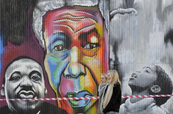 Dos mujeres caminan delante de un mural de Nelson Mandela, en Londres.