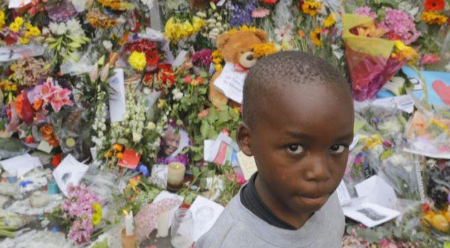 Un niño delante de las flores colocadas ante la casa de Mandela.