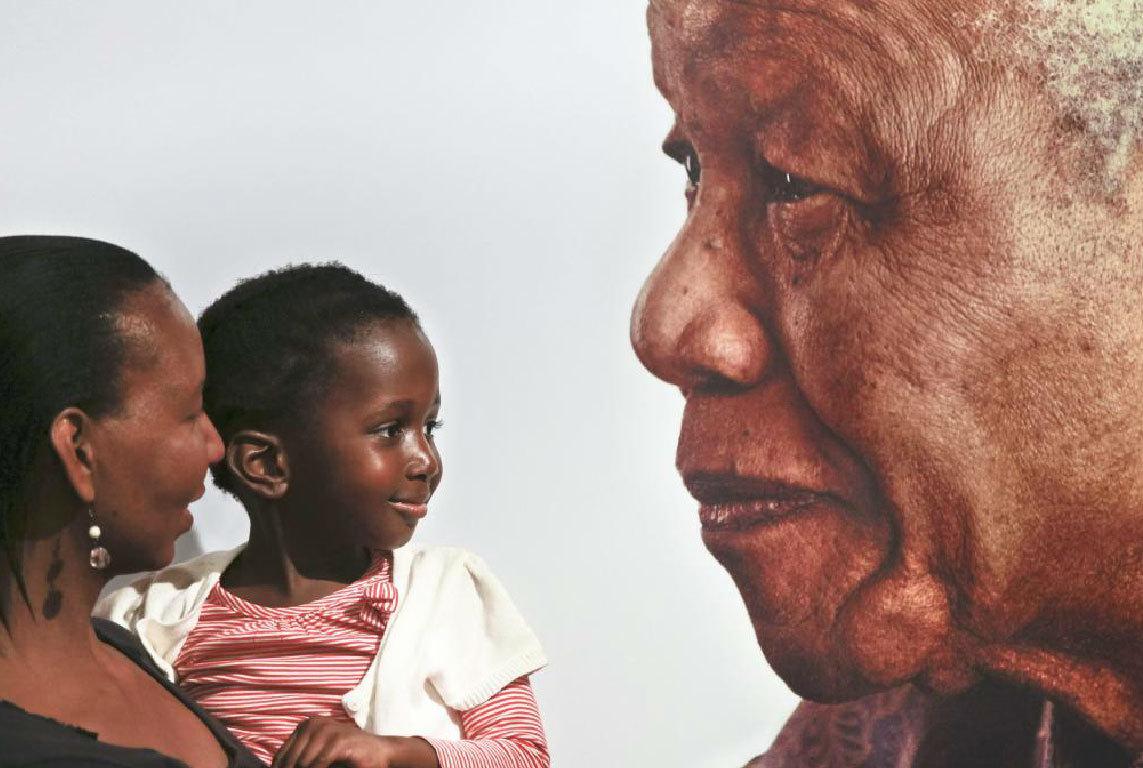 Una niña sonríe en brazos de su madre frente a un gran cartel con el...