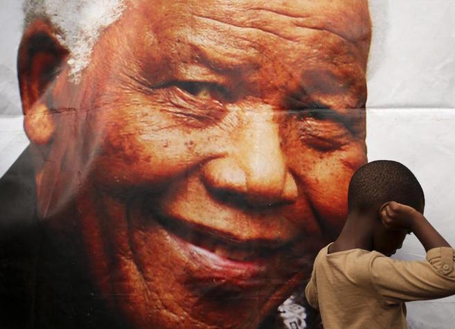 Un niño pasa junto a una foto de Nelson Mandela.