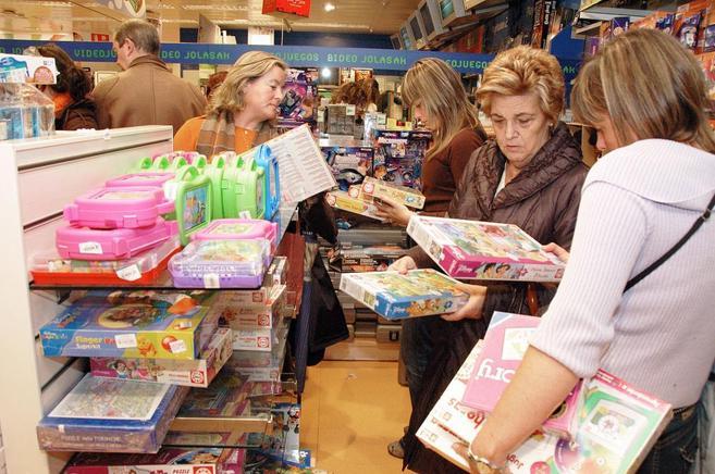 Tres mujeres observan varios juguetes , durante su jornada de compras...