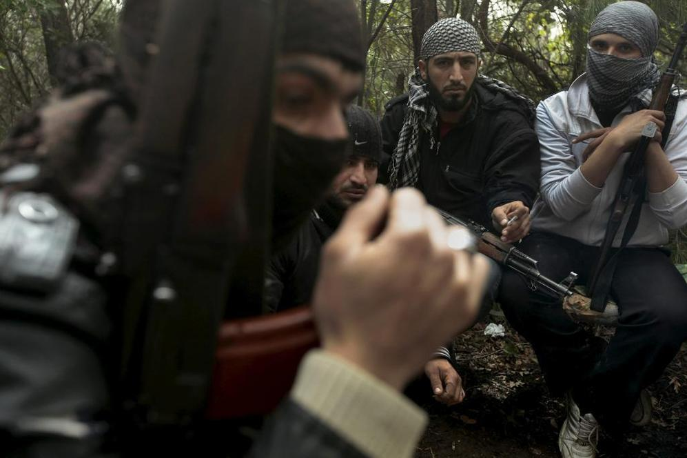Milicianos armados del Ejército Libre de Siria se reúnen en una zona...