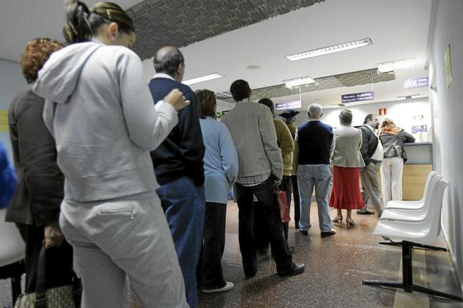 Varias personas esperan su turno para pedir cita médica en una sala...