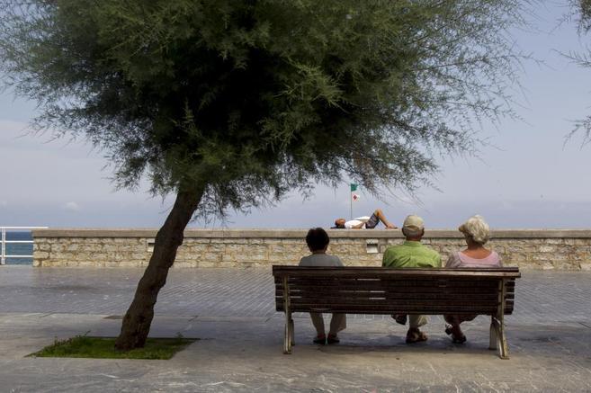 Ancianos sentados en un banco junto al Centro Kursaal en San...