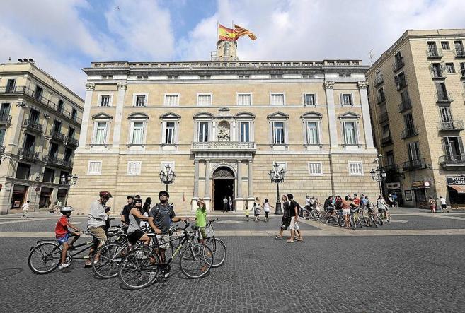 Dos grupos de ciclistas y peatones delante del Palacio de la...