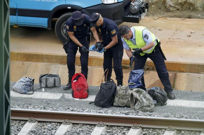 Unos policías identifican objetos de los viajeros que iban en el tren...