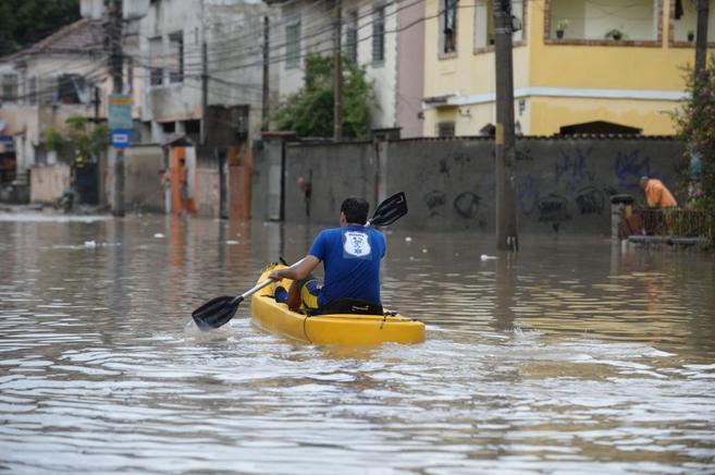 Un hombre rema para desplazarse por las calles inundadas de un...