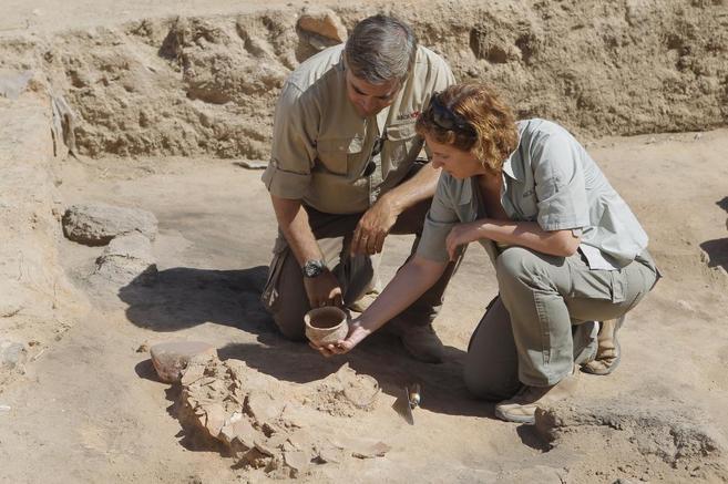 Dos arqueólogos estudian los restos extraídos de un yacimiento en...