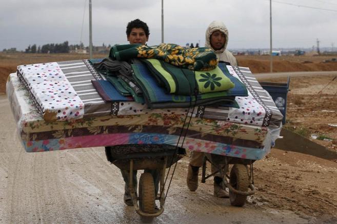 Refugiados sirios transportan sus pertenencias bajo la lluvia en el...