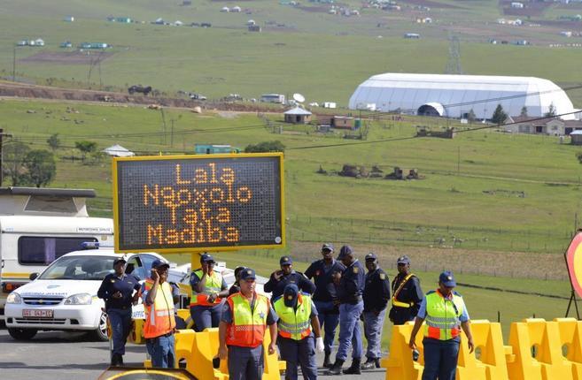 Policías bloquean la carretera que lleva a la zona donde se...