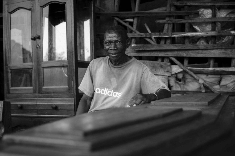 El señor Mukendi, sentado en su tienda de ataúdes.