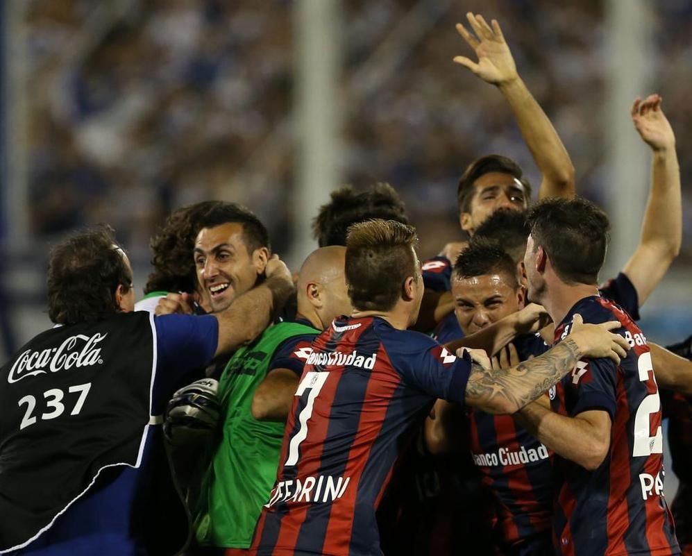 Los jugadores de San Lorenzo se abrazan en el centro del campo tras el...