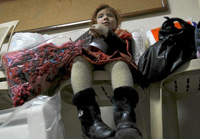 Una niña refugiada siria agarra su recipiente de leche durante un...