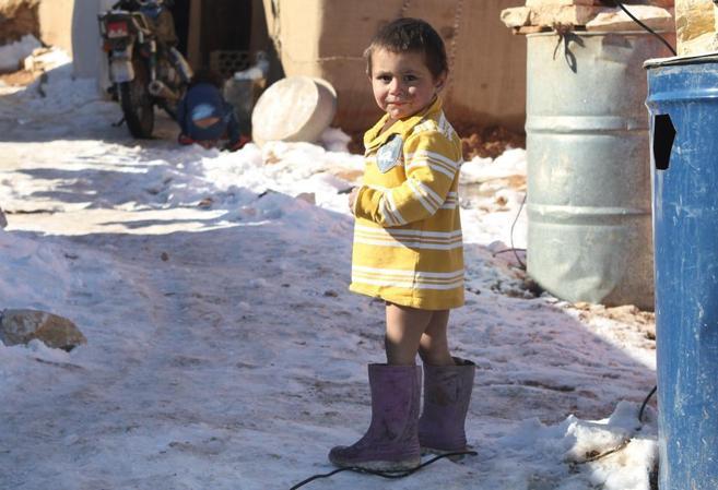 Un niño sirio parado en la nieve en un campamento improvisado de...