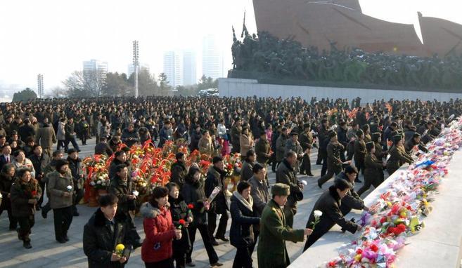 Un grupo de norcoreanos deja ofrendas florales junto a las estatuas de...