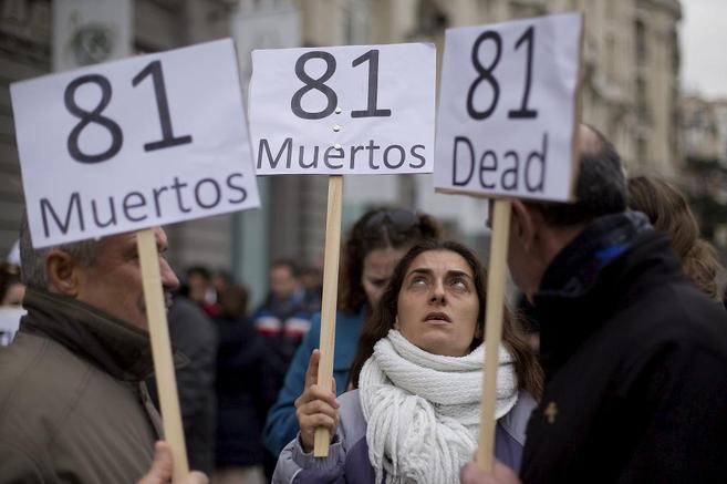 3 personas con pancartas que dice '81 muertos/dead', la mujer del...