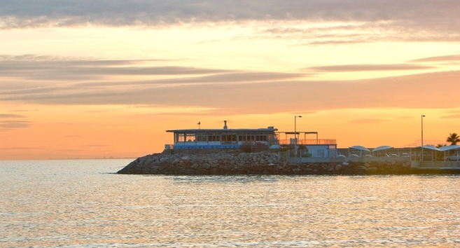 Vista del restaurante El Morro coronado por el faro de la escollera de...