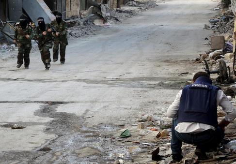 Milicianas yihadistas pasan junto a un periodista, en Alepo.