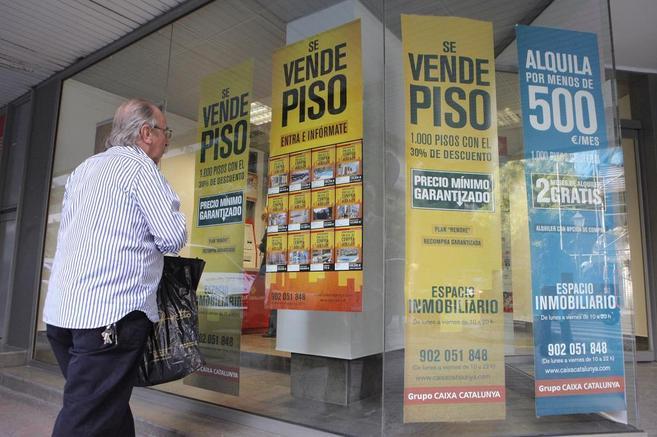 Imagen de archivo de un escaparate de un banco publicitando pisos en...