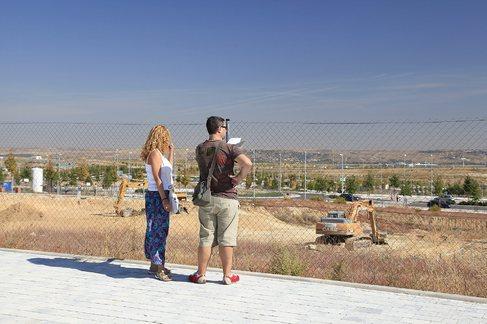 Una pareja observa unos terrenos en Valdebebas.