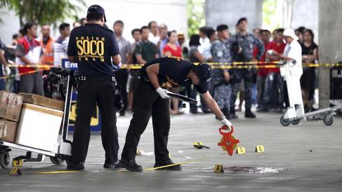 Policías inspeccionan el lugar del crimen en el aeropuerto de Manial.