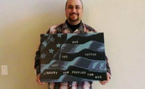 George Zimmerman posa con uno de su cuadros.