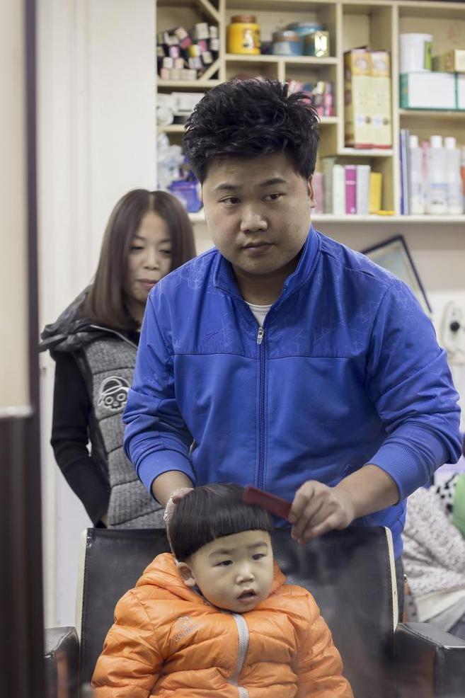 Ding Jie peina a su hijo ante su mujer, Fu Xiaofei, en su peluquería...