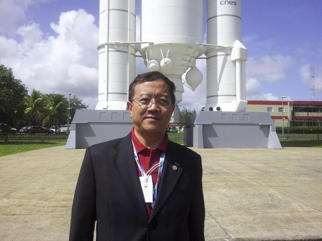 Ji Wu posa delante de la réplica de un cohete en el Puerto Espacial...