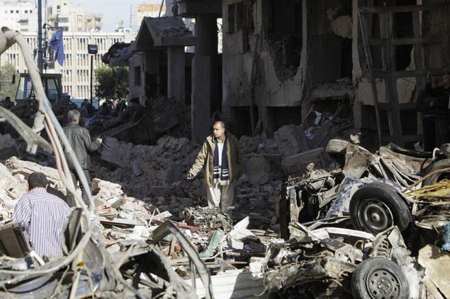 Un hombre camina entre los escombros provocados por la explosión de...