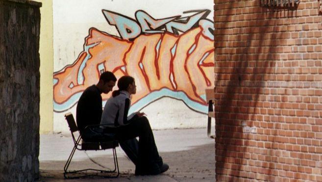 Una pareja de jóvenes, sentados en un banco en la calle.
