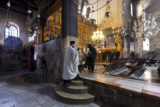 Un cura griego ortodoxo quema incienso en la Iglesia de la Natividad...